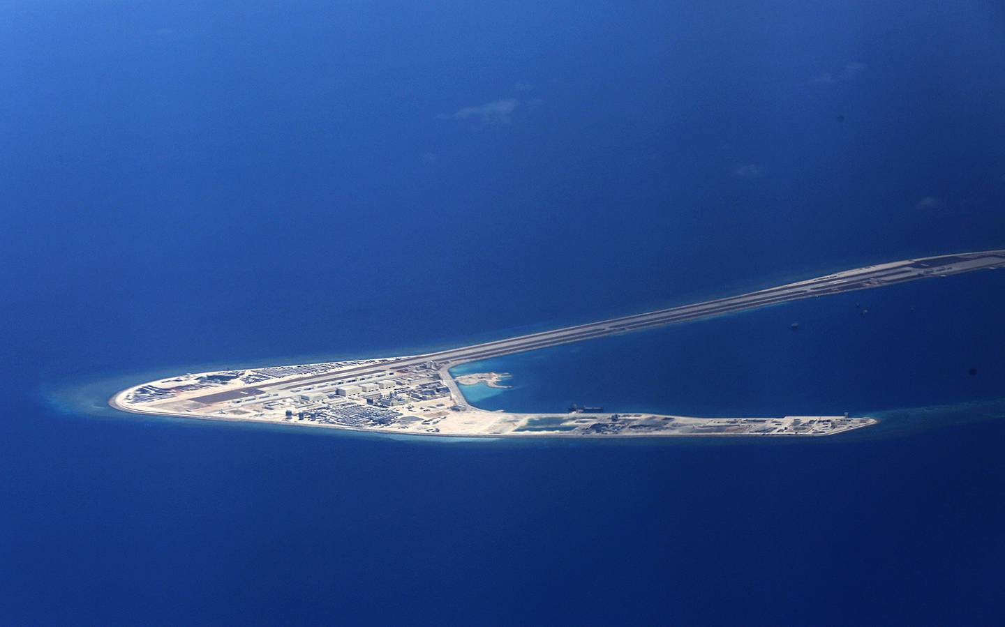 In this April 21, 2017, file photo, Chinese structures and an airstrip on the man-made Subi Reef at the Spratlys group of islands are seen from a Philippine Air Force C-130 transport plane off the disputed South China Sea in western Philippines.