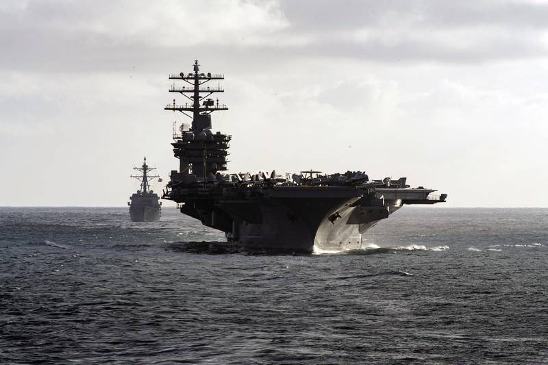 The aircraft carrier USS Nimitz (CVN 68) and Arleigh Burke-class guided-missile destroyer USS Ralph Johnson (DDG 114) steam in formation during a composite training unit exercise as part of the Nimitz Carrier Strike Group (CSG) on May 14, 2020, in the Pacific Ocean.