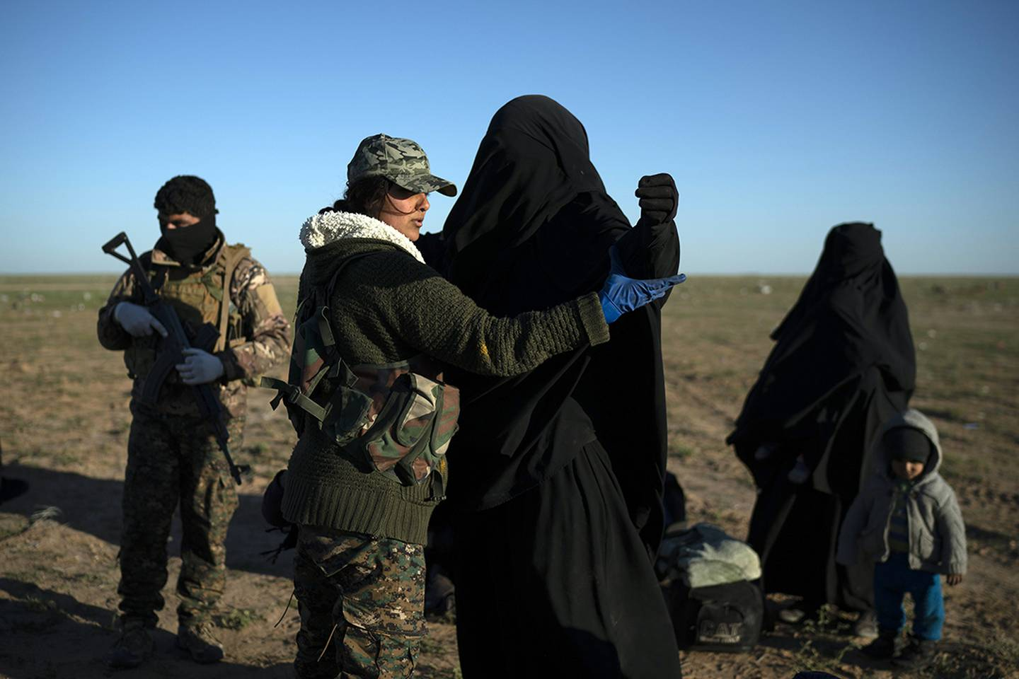 a woman is frisked by a U.S.-backed Syrian Democratic Forces fighter at a screening area after being evacuated out of the last territory held by Islamic State group militants.