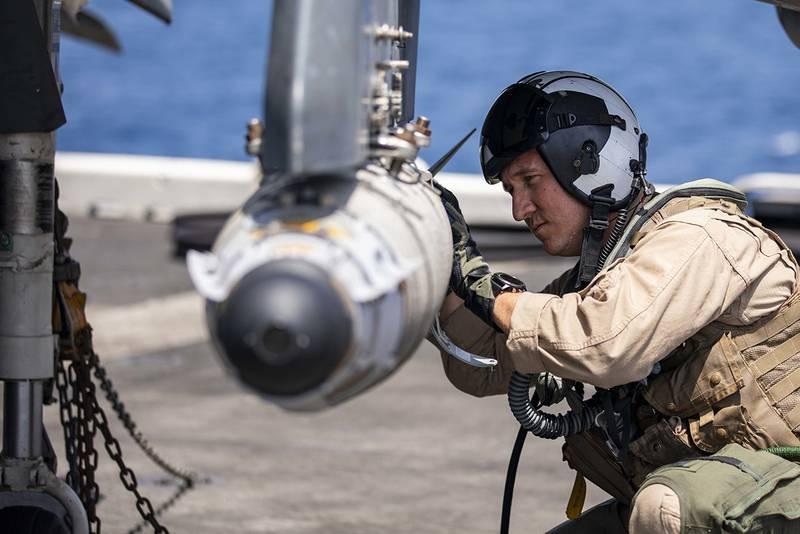 AV-8HB Harrier pilot Maj. Joseph Swindell inspects a GBU-54 joint direct attack munition during pre-flight checks May 20, 2019, on the flight deck of the Wasp-class amphibious assault ship USS Kearsarge (LHD 3) in the Arabian Sea.