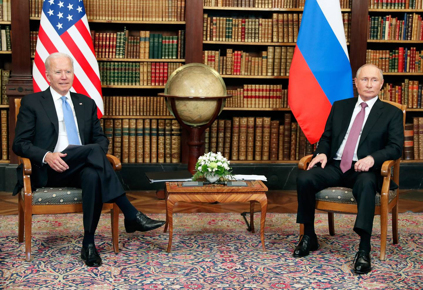 The leaders of the United States and Russia are seated with their nations' flags behind them in a library setting.