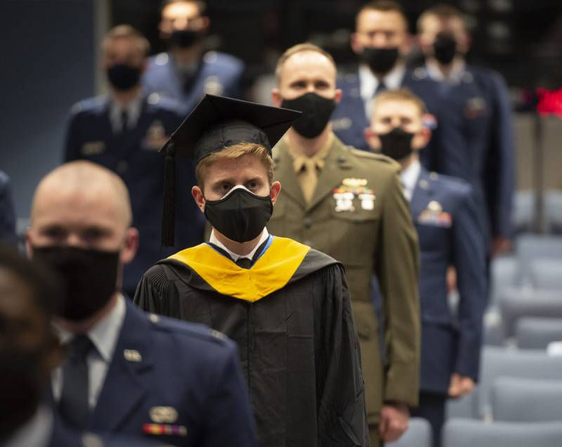 Nathan R. Boone and his classmates take their seats at the start of the Air Force Institute of Technology graduation ceremony March 25, 2021, at Wright-Patterson Air Force Base, Ohio. Approximately 250 advanced degrees were awarded to airmen and Space Force guardians. (R.J. Oriez/Air Force)
