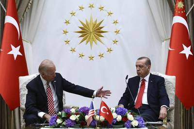 Then-Vice President Joe Biden, left, speaks with Turkish President Recep Tayyip Erdogan as they sit in front of flags for Turkey.