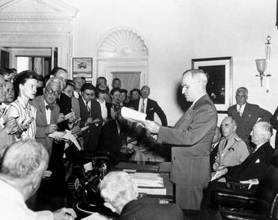 In this Aug. 14, 1945, file photo, President Harry S. Truman reads to newsmen his announcement of the Japanese surrender, officially signaling the war's end.