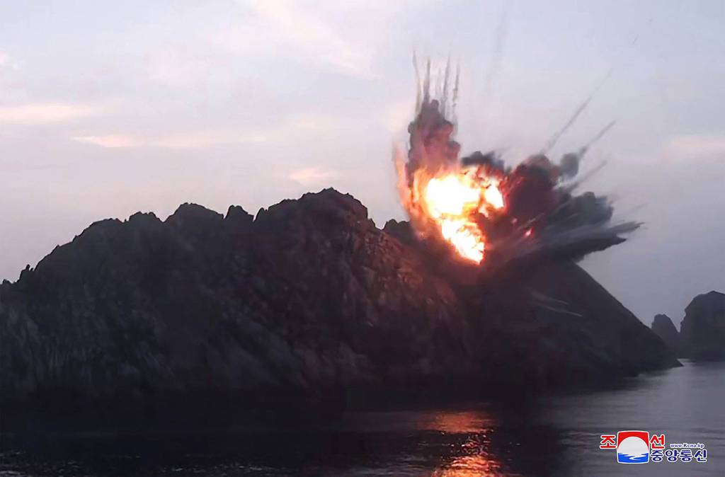 This Aug. 6, 2019, photo provided by the North Korean government shows what it says is a new type of tactical guided missile launched from an airfield in the western area of North Korea landing in an islet in waters off the country's eastern coast.