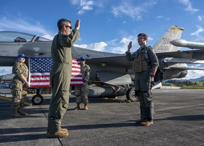 U.S. Air Force Maj. Joseph Butters administers the oath of office to U.S. Air Force Capt. Devin Mulvanny at a promotion ceremony during Exercise Relampago VI at Comando Aereo de Combate Number 5 in Rionegro, Colombia, on July 19, 2021. (Senior Airman Duncan Bevan/Air Force)