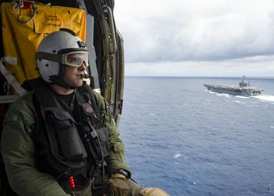 Naval Air Crewman (Helicopter) 3rd Class Jake Shelton observes the Nimitz-class aircraft carrier USS Harry S. Truman (CVN 75) in the Atlantic Ocean on May 27, 2020.