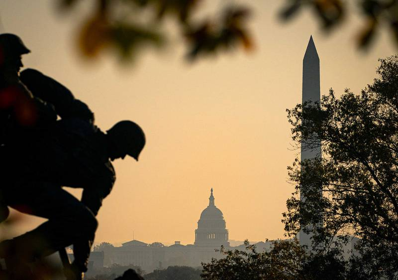 The U.S. Marine Corp's Iwo Jima Memorial can be seen as the morning sun begins to rise behind the U.S. Capitol and Washington Monument on Nov. 7, 2020, in Arlington, Va.
