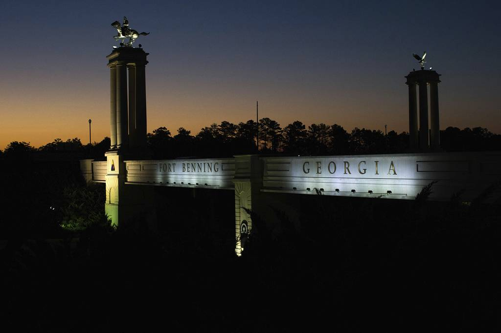 In this Oct. 16, 2015, file photo a bridge marks the entrance to the U.S. Army's Fort Benning as the sun rises in Columbus, Ga.
