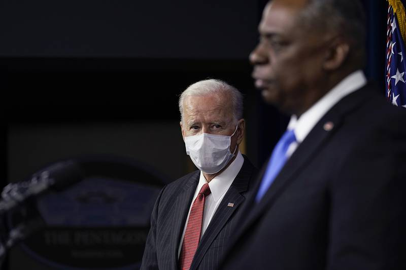 President Joe Biden listens as Secretary of Defense Lloyd Austin speaks at the Pentagon, Wednesday, Feb. 10, 2021, in Washington.