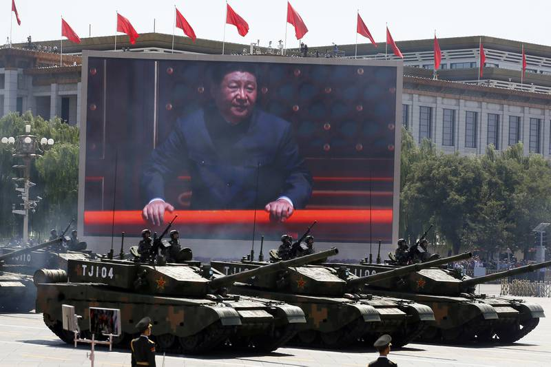 In this Sept. 3, 2015, file photo, Chinese President Xi Jinping is displayed on a screen as Type 99A2 Chinese battle tanks take part in a parade commemorating the 70th anniversary of Japan's surrender during World War II held in front of Tiananmen Gate in Beijing.