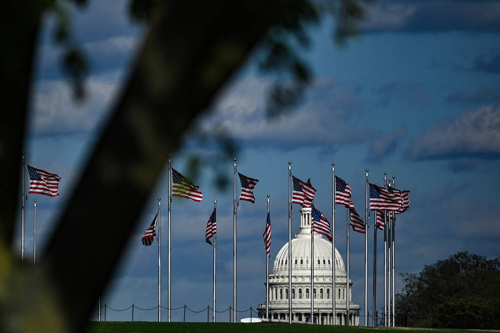 The dome of the U.S. Capitol building is seen behind a row of U.S. flags on April 10, 2020, in Washington.