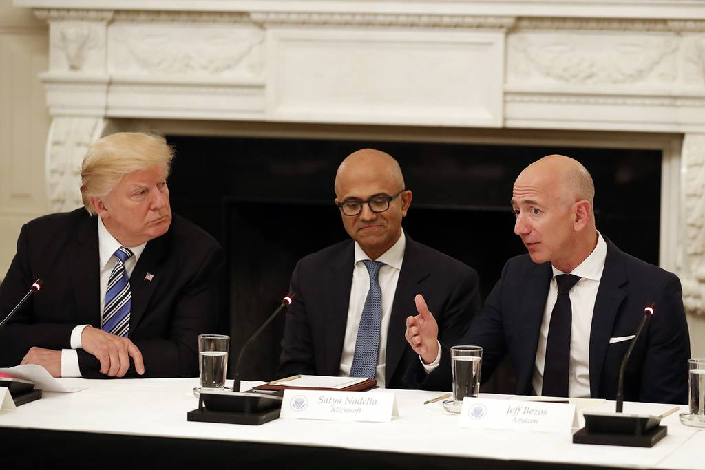 In this June 19, 2017, file photo President Donald Trump, left, and Satya Nadella, chief executive officer of Microsoft, center, listen as Jeff Bezos, chief executive officer of Amazon, speaks during an American Technology Council roundtable in the State Dinning Room of the White House in Washington.