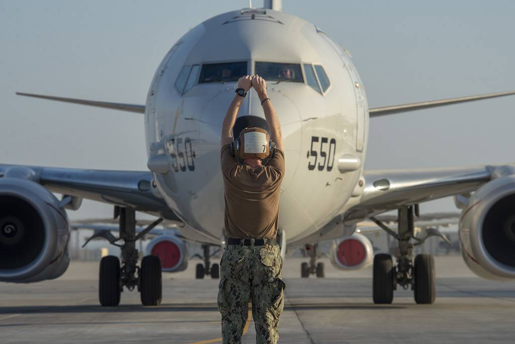 Culinary Specialist Seaman Tyler Stender directs a P-8A Poseidon maritime patrol and reconnaissance aircraft on Nov. 24, 2020, in the U.S. 5th Fleet area of operations.