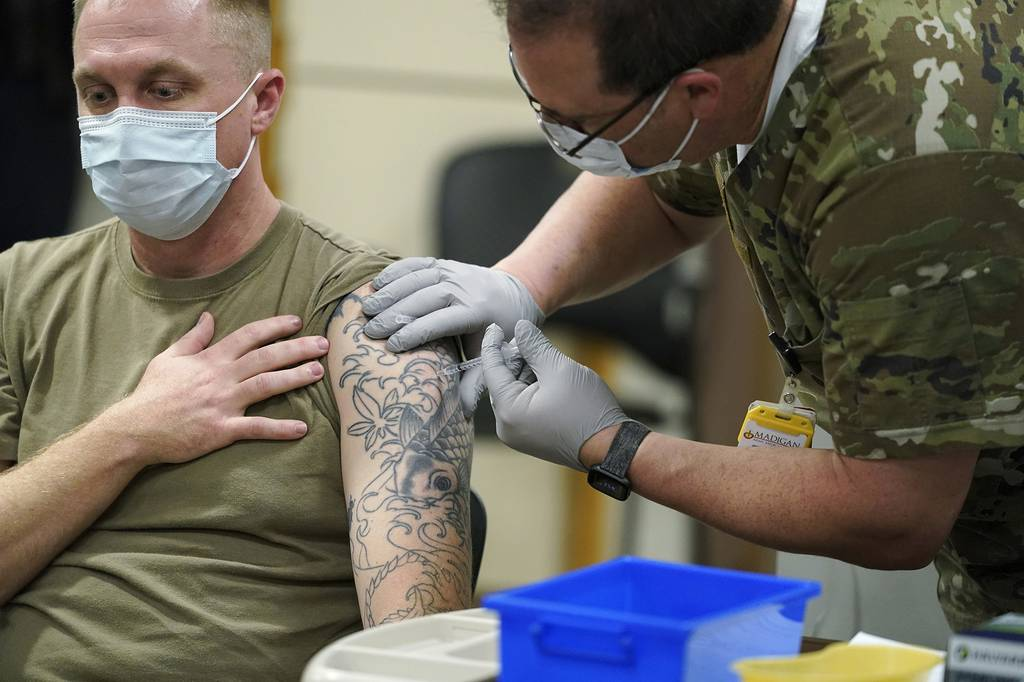 A seated and masked soldier receives a vaccination shot in his tattooed arm.