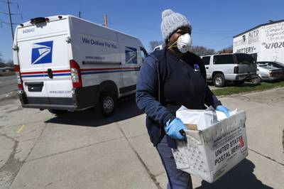 In this April 2, 2020, file photo, a United States Postal  Service worker makes a delivery with gloves and a mask in Warren, Mich.