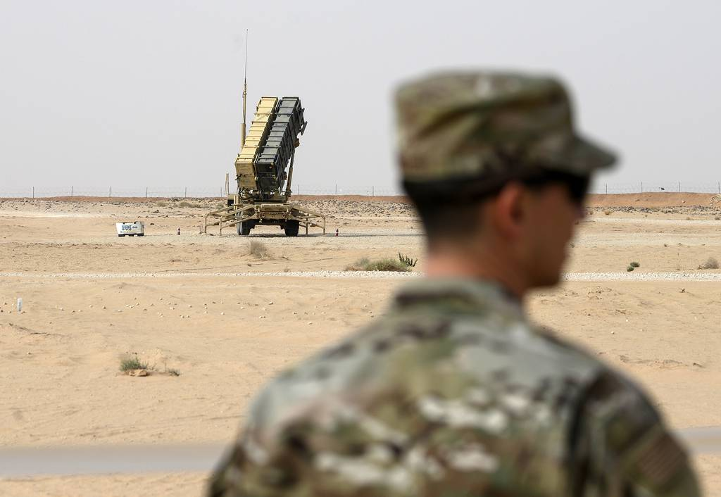 a member of the U.S. Air Force stands near a Patriot missile battery at the Prince Sultan air base in al-Kharj, central Saudi Arabia.