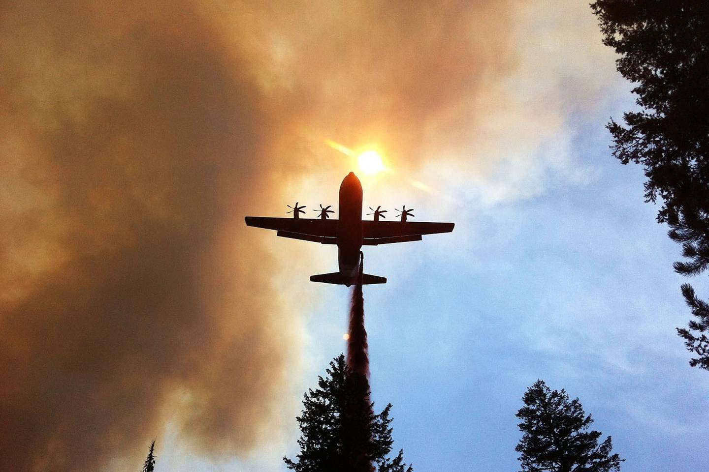 WILDFIRE ASSISTANCE -- A California Air National Guard C130-J Hercules, equipped with Modular Airborne Firefighting System, drops retardant on a wildfire near Twin Falls, Idaho, Aug. 8, 2012. (DOD photo)