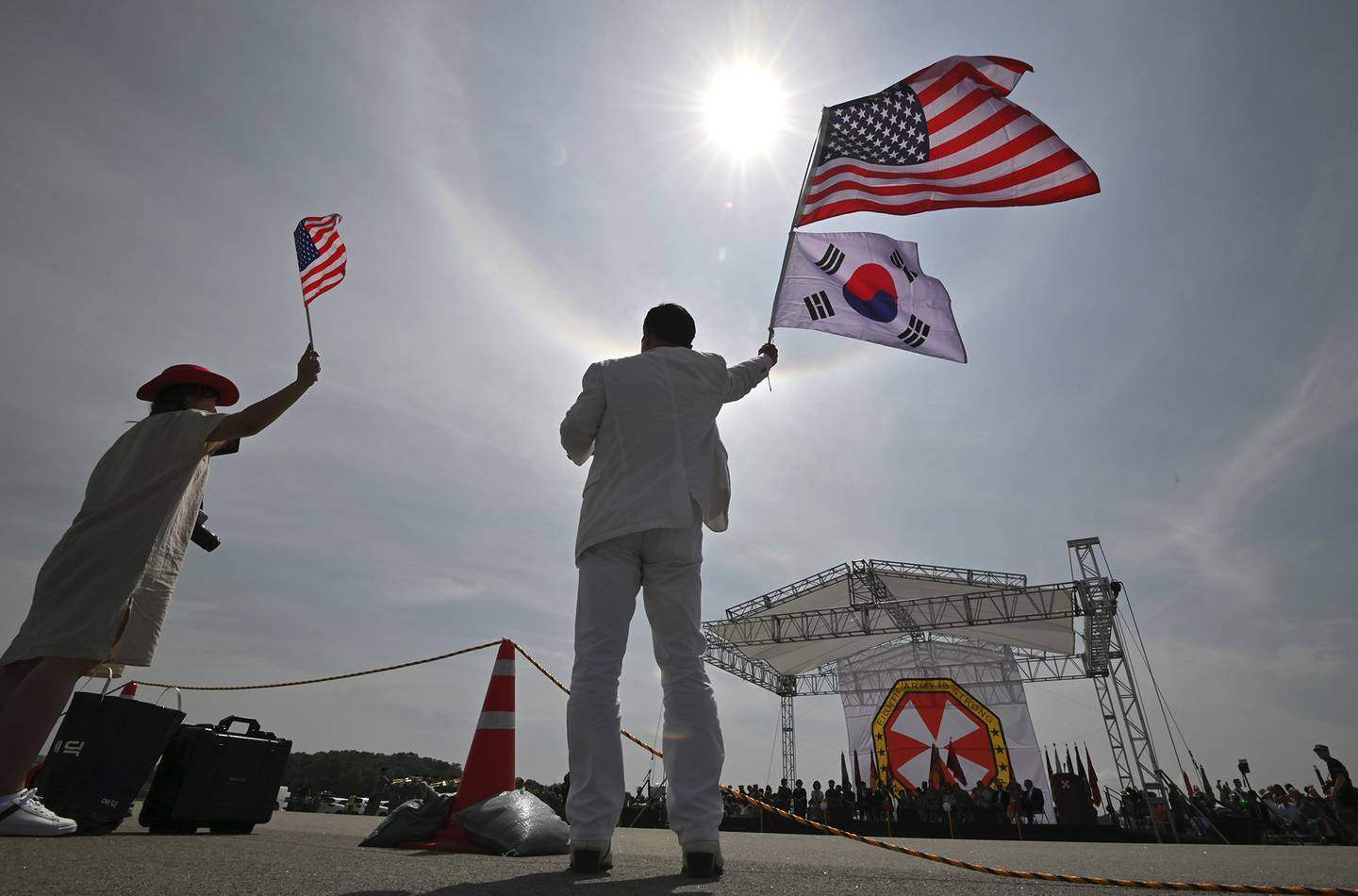 A man and a woman wave flags during a ceremony to commemorate the 75th anniversary of the Eighth U.S. Army at Camp Humphreys in Pyeongtaek on June 8, 2019.