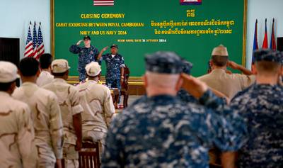 Capt. Fred Kacher, commander of Destroyer Squadron (DESRON) 7, and Rear Adm. Ros Veasna, deputy commander of Ream Naval Base, salute during the closing ceremony of Cooperation Afloat Readiness and Training (CARAT) Cambodia 2014.