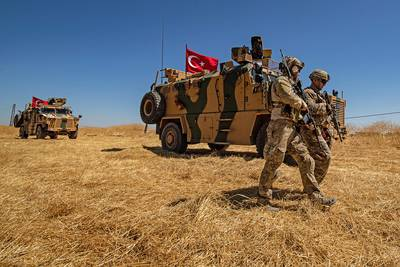 U.S. troops walk past a Turkish military vehicle during a joint patrol with Turkish troops