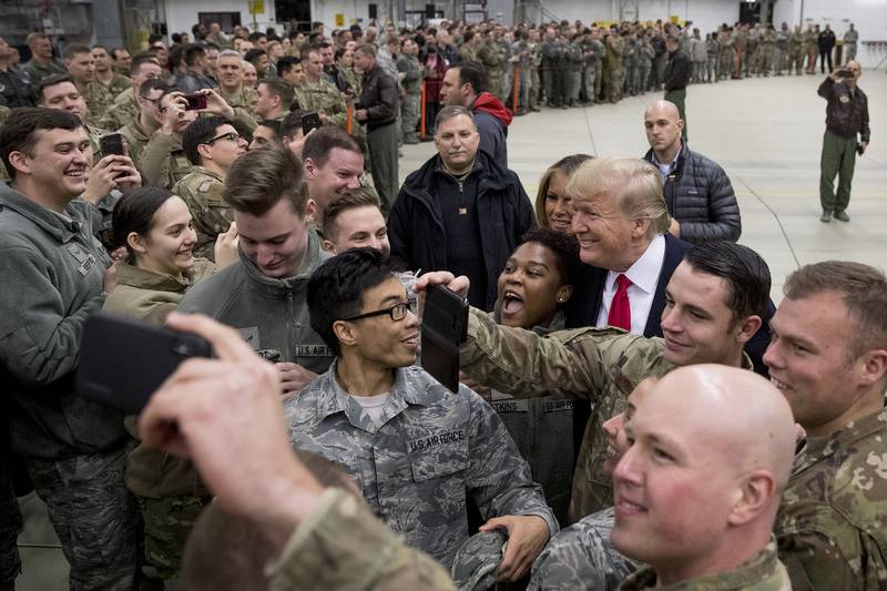 In this Dec. 27, 2018, file photo, President Donald Trump, center right, and first lady Melania Trump, center left, greet members of the military at Ramstein Air Base, Germany.