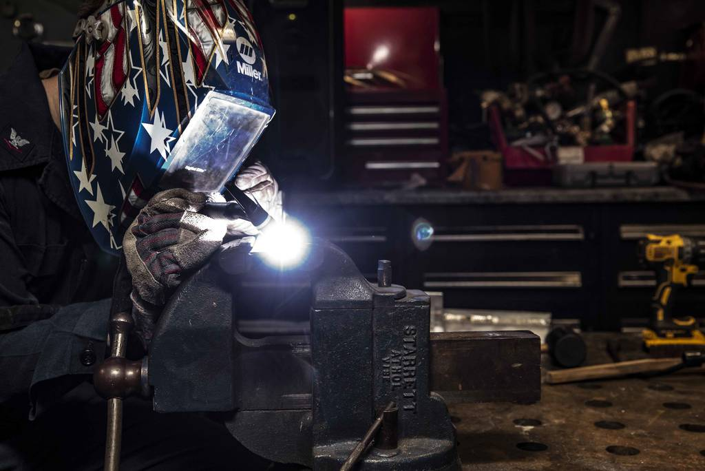 Hull Maintenance Technician 3rd Class Drew Knutson welds stainless steel and aluminum angles in the repair shop of the aircraft carrier USS Ronald Reagan (CVN 76) on July 8, 2020, in the South China Sea.
